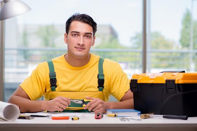 Bauarbeiter, der am schreibtisch sitzt