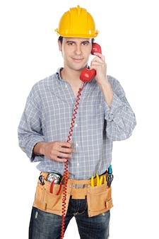 Bauarbeiter, der am telefon über weißem hintergrund spricht