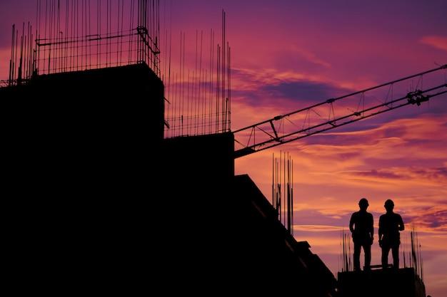 Bauarbeiter, der an einer baustelle arbeitet, damit bauteams in der schwerindustrie arbeiten