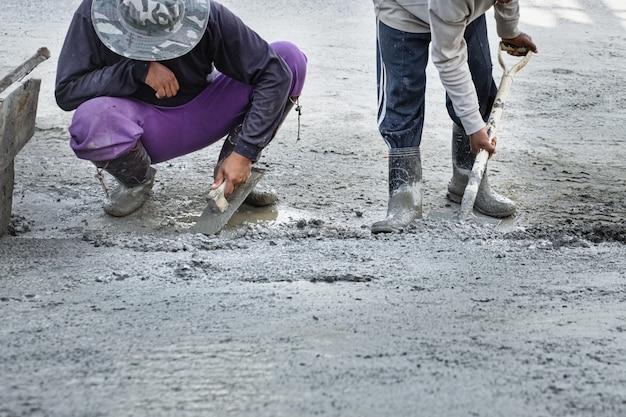 Bauarbeiter, der an gipszement für boden im neuen haus arbeitet.