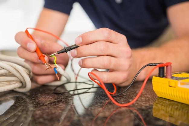 Bauarbeiter, der an kabeln arbeitet