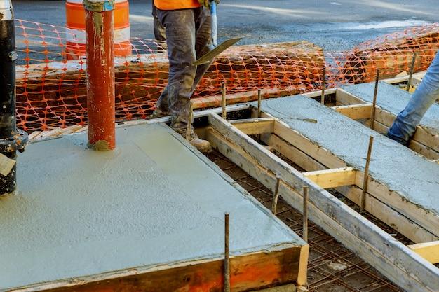 Bauarbeiter, der betondecke ausrichtet. betonpflaster gießen