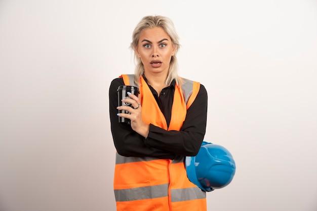 Bauarbeiter, der bruch mit tasse tee auf weißem hintergrund hat. hochwertiges foto