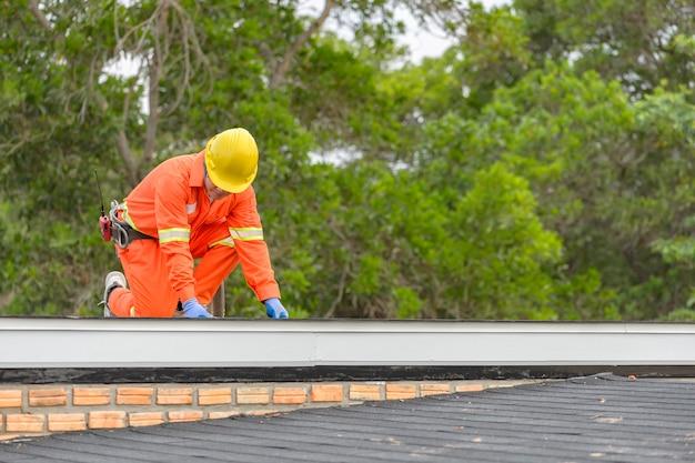 Bauarbeiter, der das asphaltdach (schindeln) mit nagelpistole auf eine große gewerbliche wohngebäudeentwicklung setzt Premium Fotos