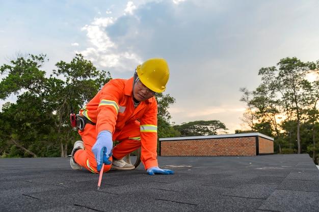 Bauarbeiter, der das asphaltdach (schindeln) mit nagelpistole auf eine große gewerbliche wohngebäudeentwicklung setzt