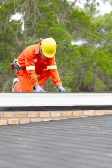 Bauarbeiter, der das asphaltdach setzt