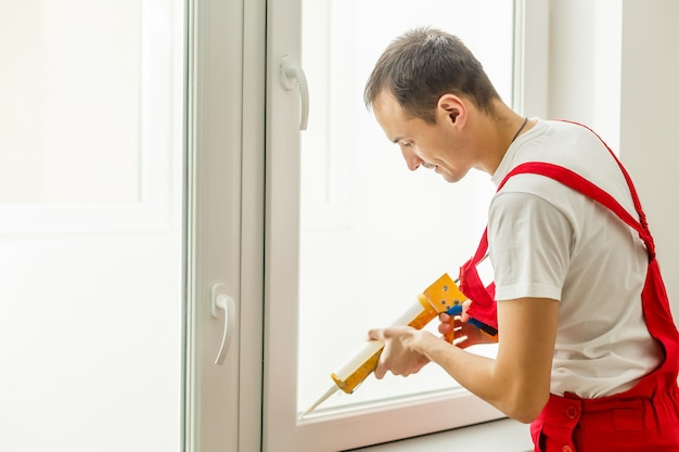 Bauarbeiter, der dichtungsschaumband auf fenster in haus einsetzt