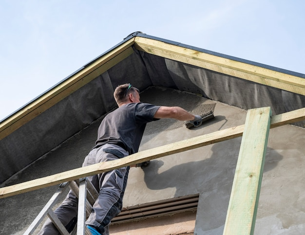 Bauarbeiter, der die fassade des hauses verputzt. auftragen von fassadenputz