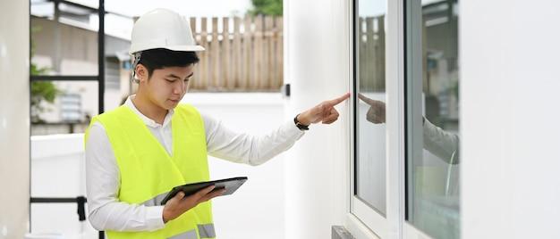 Bauarbeiter, der digitales tablett für scheckhausbau verwendet