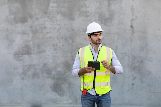 Bauarbeiter, der digitales tablettenisolat auf grauem zementhintergrund hält und betrachtet. projektingenieur auf der baustelle.