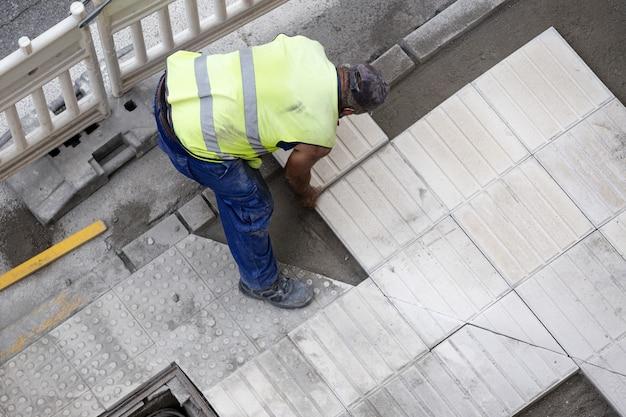 Bauarbeiter, der eine fliese legt, die einen bürgersteig repariert. wartungskonzept