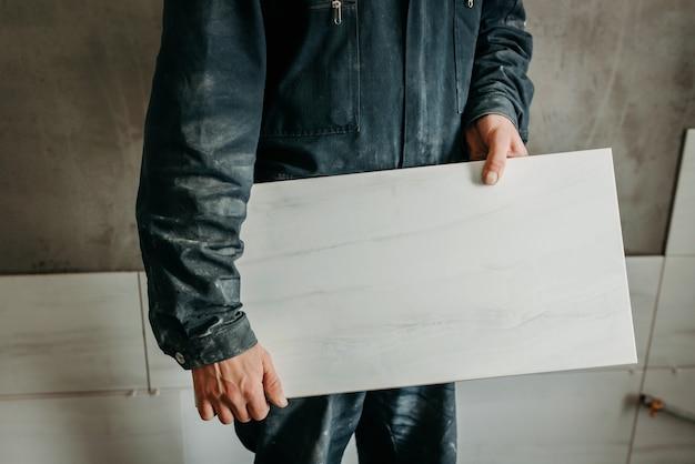 Bauarbeiter, der eine große wandfliese hält