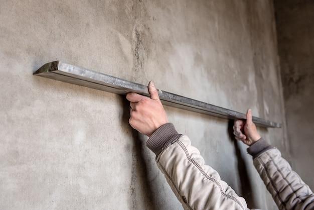 Bauarbeiter, der eine wand mit richtmaschine verputzt