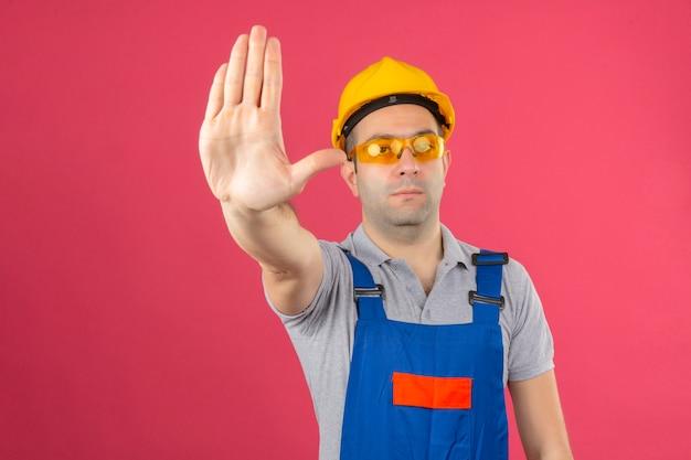 Bauarbeiter, der einen einheitlichen schutzhelm und eine brille trägt, die stoppgeste mit der hand machen, die ernsthaft auf rosa lokalisiert aussieht