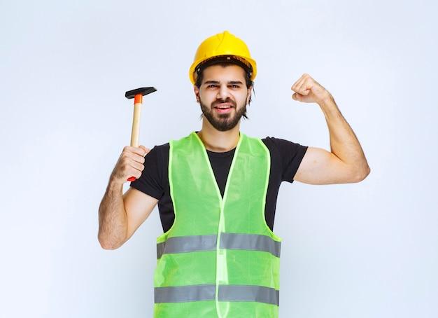 Bauarbeiter, der einen klauenhammer hält und sich mächtig fühlt.
