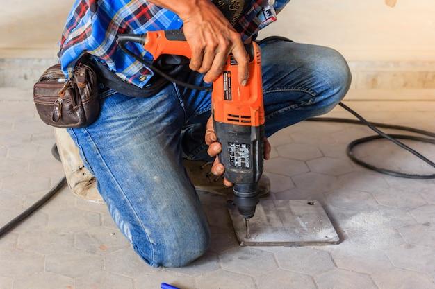 Bauarbeiter, der elektrische bohrmaschine verwendet, um stahlplatte in eine baustelle zu installieren.