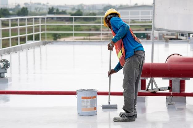 Bauarbeiter, der epoxidfarbe an der dachplatte für wasserdichten schutz beschichtet