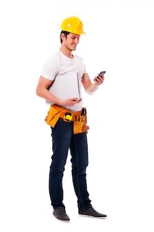 Bauarbeiter, der etwas auf dem mobiltelefon überprüft