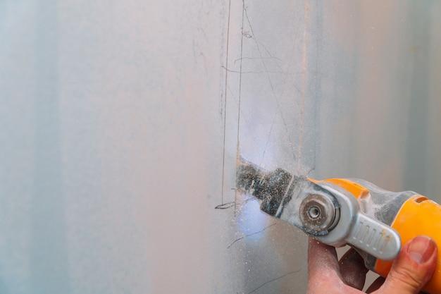 Bauarbeiter, der gipskartonplatte unter verwendung des winkelschleifers des elektrischen schneiders schneidet