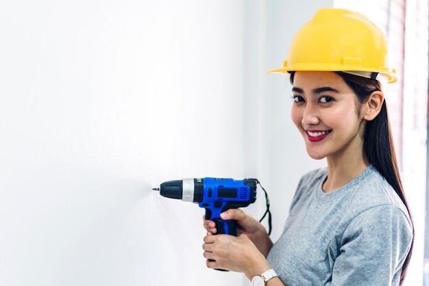 Bauarbeiter der jungen frau, der mit schraubenzieher arbeitet, um einen hauseingang herein zu bohren