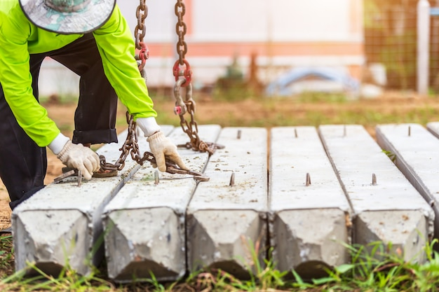 Bauarbeiter, der konkrete stange vom lkw entlädt