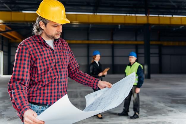 Bauarbeiter, der lichtpausen überprüft