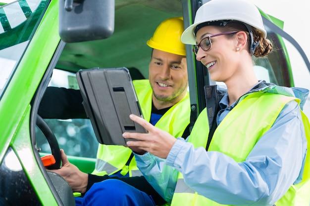 Bauarbeiter, der mit ingenieurplänen sich bespricht