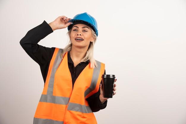 Bauarbeiter, der mit tasse tee auf weißem hintergrund aufwirft. hochwertiges foto