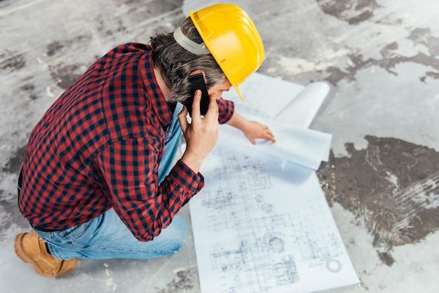 Bauarbeiter, der pläne überprüft und am telefon spricht