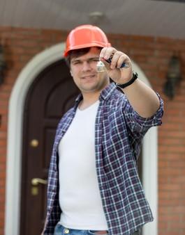 Bauarbeiter, der schlüssel vom neuen haus in der hand hält