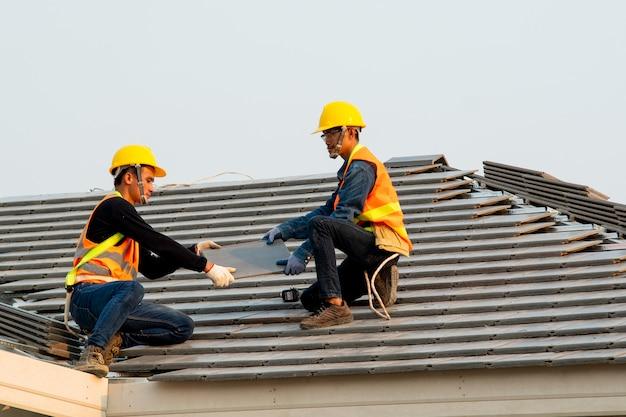 Bauarbeiter, der sicherheitsgurtgürtel während der arbeit trägt, die betondachziegel auf dem neuen dach installiert, konzept des im bau befindlichen wohngebäudes.