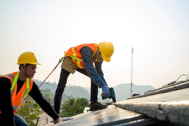 Bauarbeiter, der sicherheitsgurtgurt während der arbeit an der dachkonstruktion des gebäudes auf neuem dach trägt.