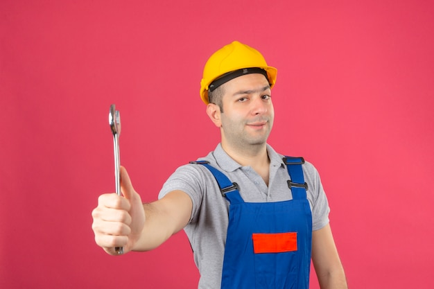 Bauarbeiter, der uniform und schutzhelm hält schlüssel in der hand mit unzufriedenem ausdruck auf rosa isoliert hält