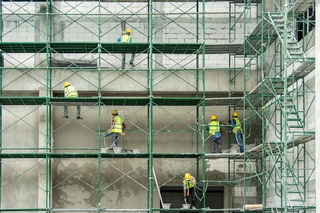 Bauarbeiter, der wand auf baugerüst vergipst