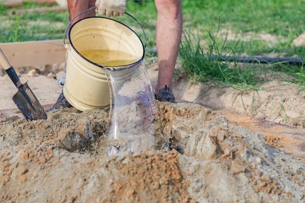 Bauarbeiter, der wasser zur mischung des sandes und des zements arming ist. zement auf der baustelle herstellen,