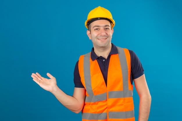 Bauarbeiter, der weißen schutzhelm und eine weste trägt, mit einem lächeln auf gesicht, das mit handfläche auf kopierraum auf blau lokalisiert zeigt
