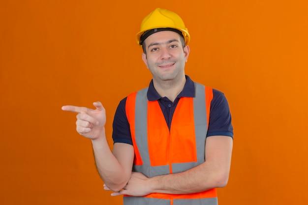 Bauarbeiter, der weste und gelben schutzhelm trägt, zeigt seinen zeigefinger seitwärts mit einem lächeln auf gesicht lokalisiert auf orange