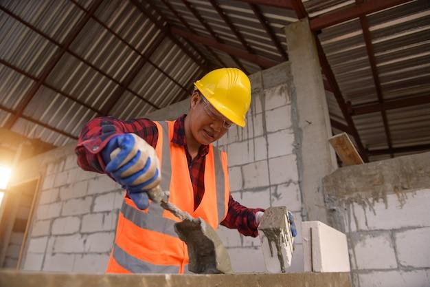 Bauarbeiter, der ziegelsteine legt und grill im industriegelände baut