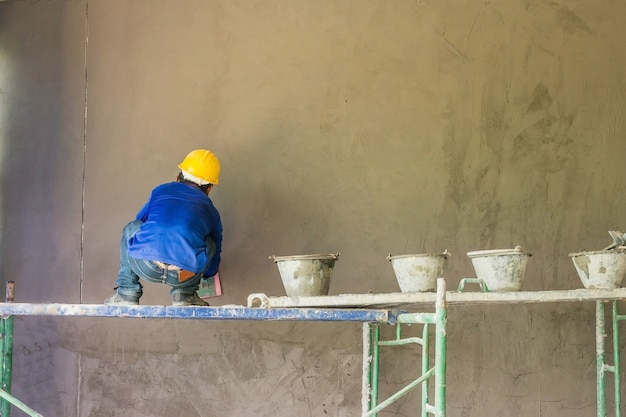 Bauarbeiter, die gebäudewand unter verwendung des zementgips verputzen