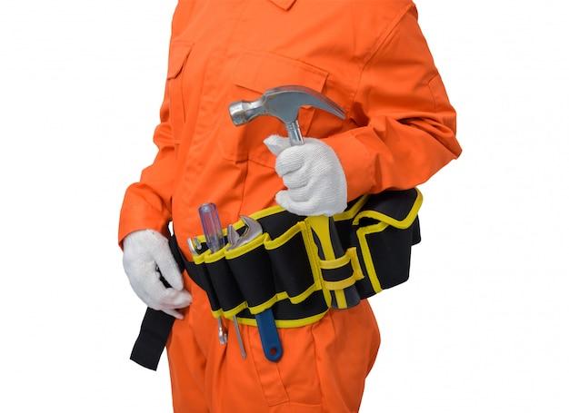 Bauarbeiter, die orange schutzkleidung, sturzhelmhand hält hammer mit dem werkzeuggurt lokalisiert auf weißem backround tragen