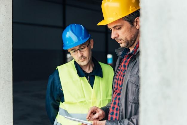 Bauarbeiter, die pläne auf tablette überprüfen