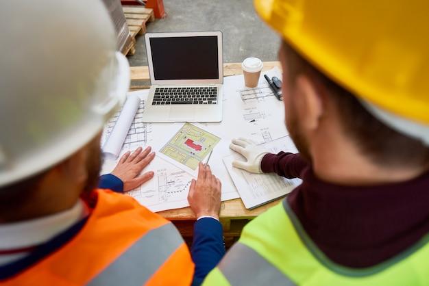 Bauarbeiter, die pläne betrachten