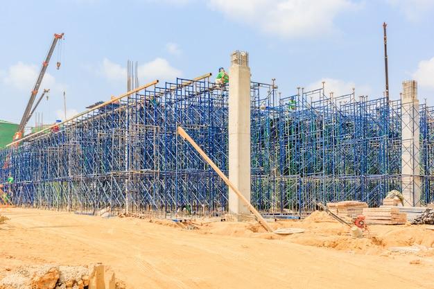 Bauarbeiter, die sicherheitsgurt tragen und baugerüst auf hohem niveau installieren