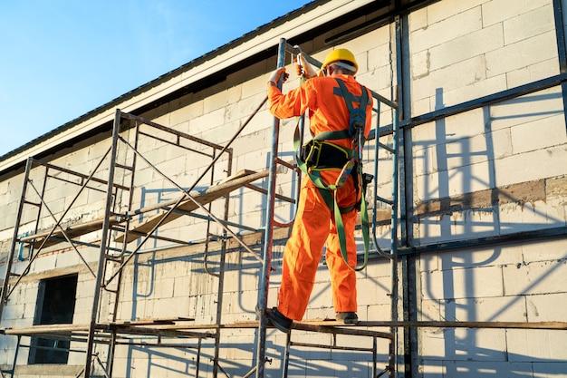 Bauarbeiter, die sicherheitsgurt während der arbeit am hohen platz tragen