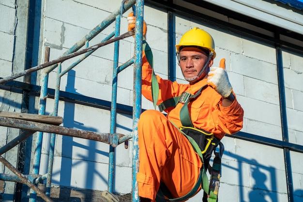 Bauarbeiter, die während der arbeit auf der baustelle eine sicherheitsleine tragen.
