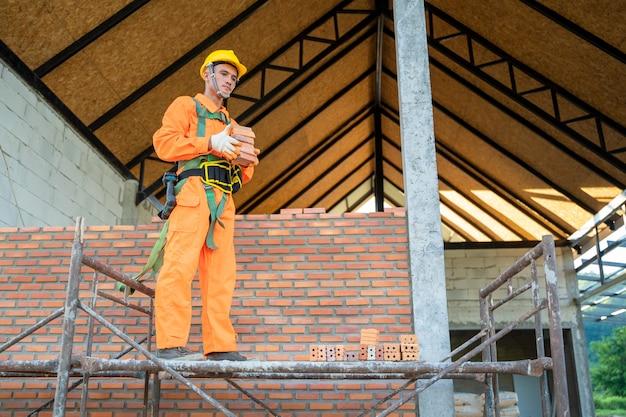 Bauarbeiter, die ziegel auf der baustelle installieren.