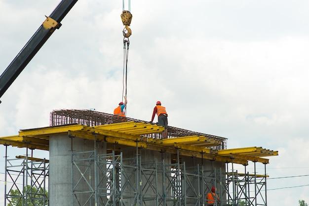 Bauarbeiter entfernen ladung von einem kran auf einer baustelle