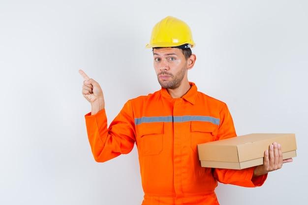 Bauarbeiter hält pappkarton und zeigt auf die linke ecke in uniform, helmvorderansicht.