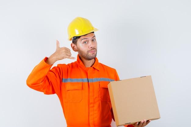 Bauarbeiter hält pappkarton, zeigt telefongeste in uniform, helm und sanft aussehend. vorderansicht.