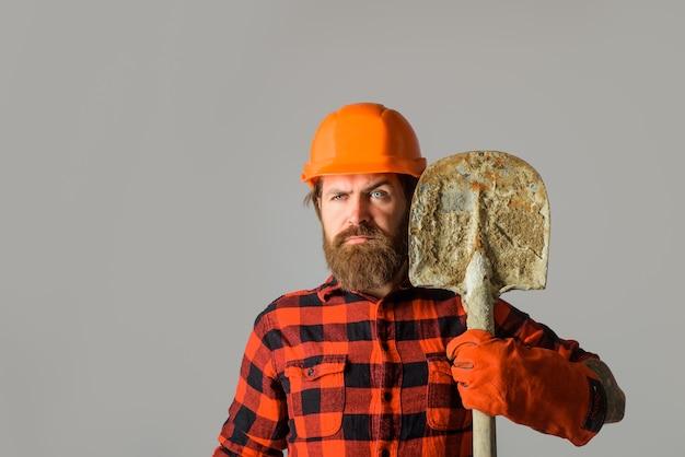 Bauarbeiter hält schaufelreparaturarbeiter mit spatenbauer in arbeitshandschuhen halten spaten